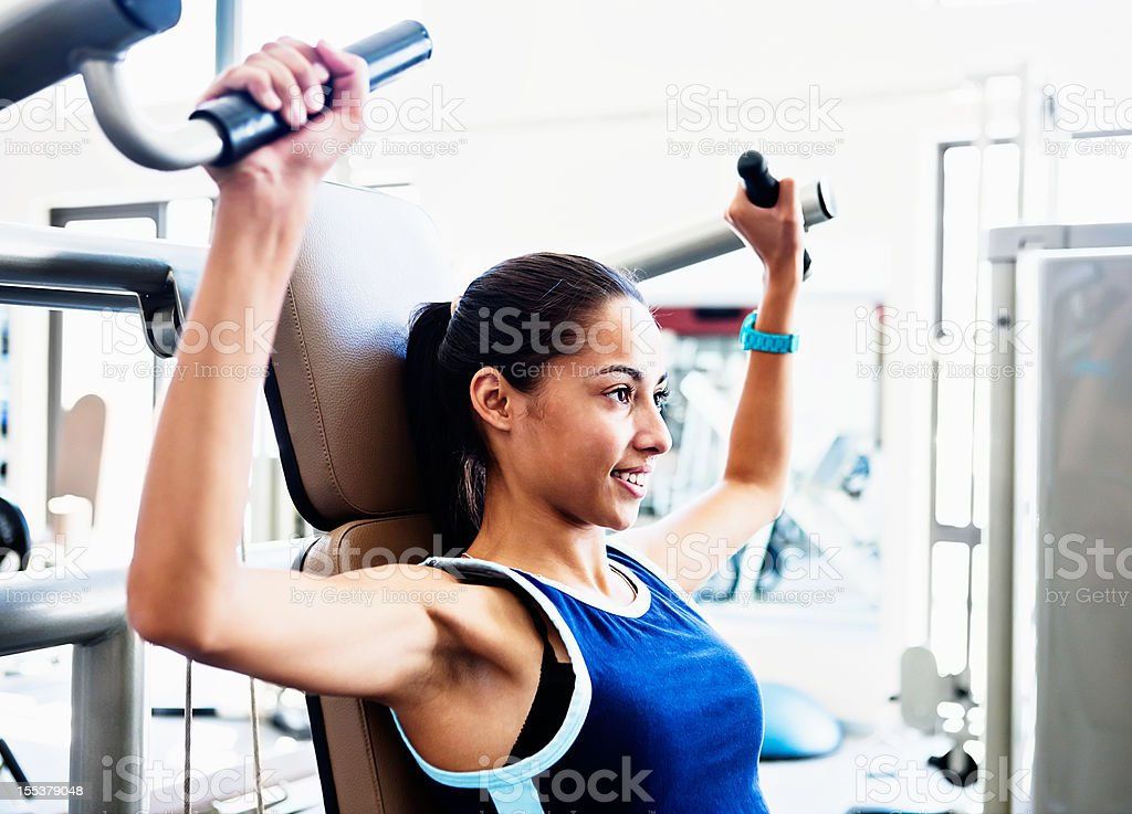 Pretty young woman does strengthening exercises in gym smiling stock photo