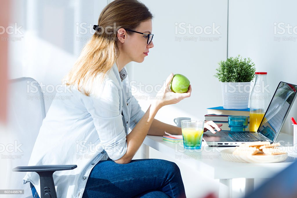 Pretty young woman eating an apple and working at home. stock photo