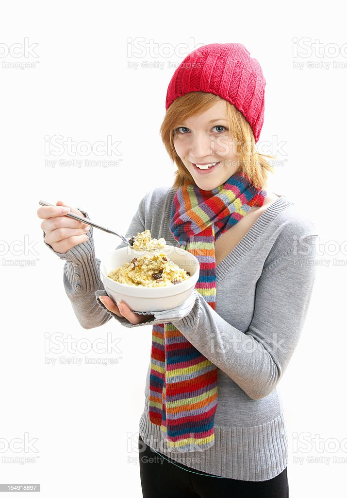 Pretty young woman eating oatmeal stock photo