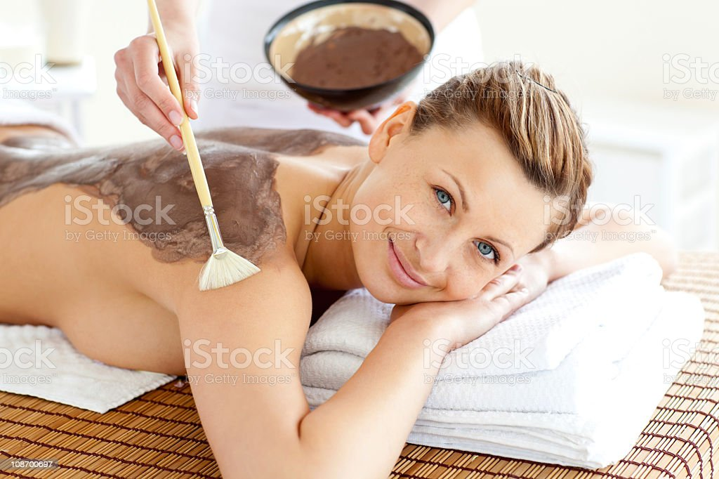 Pretty young woman enjoying a beauty treatment with mud royalty-free stock photo
