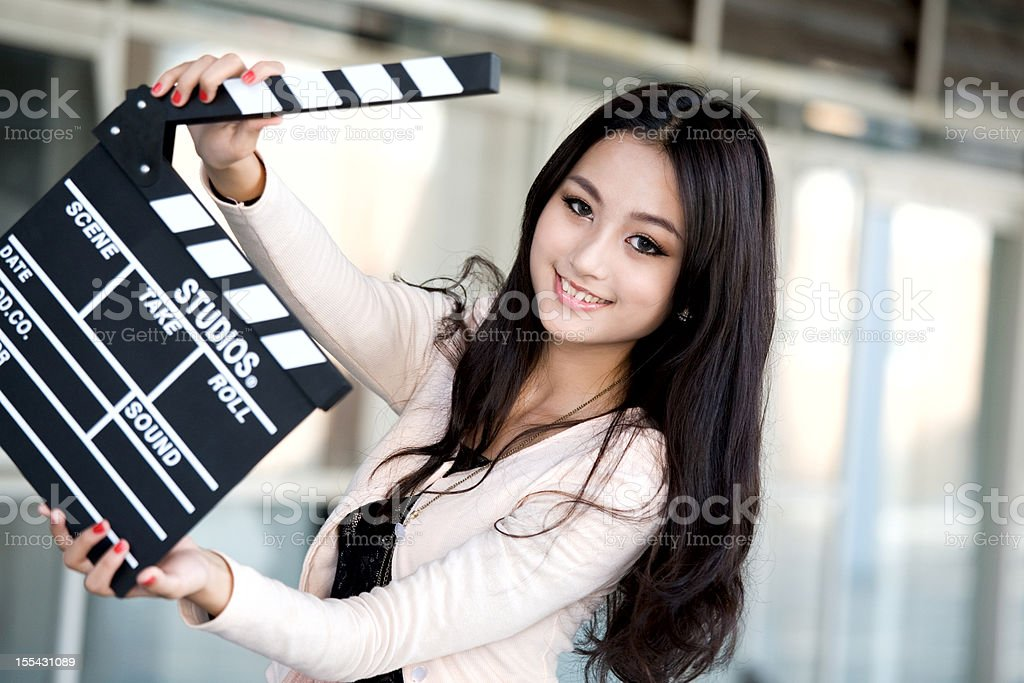 Pretty young woman holding a clapper stock photo