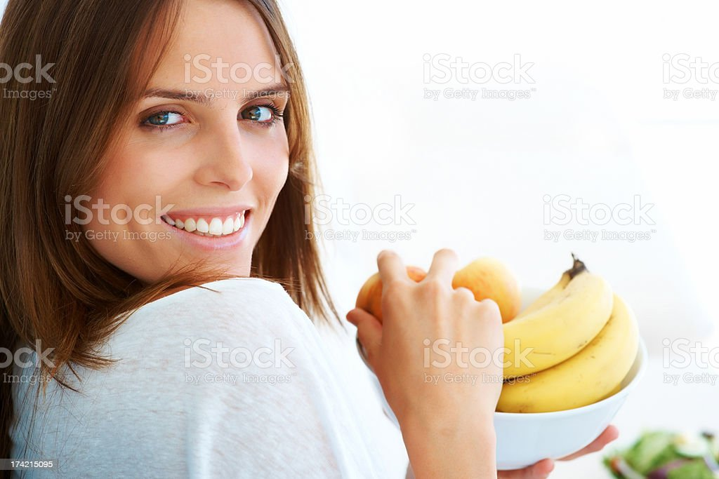 Pretty young woman holding a fruit bowl stock photo