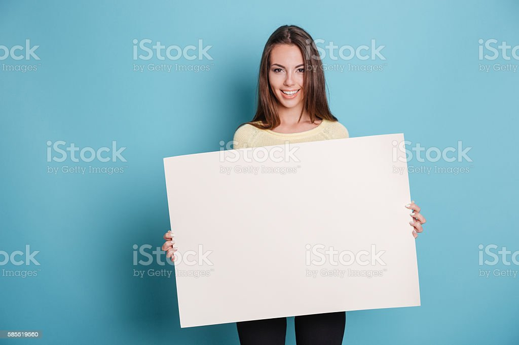 Pretty young woman holding empty blank board over blue background stock photo