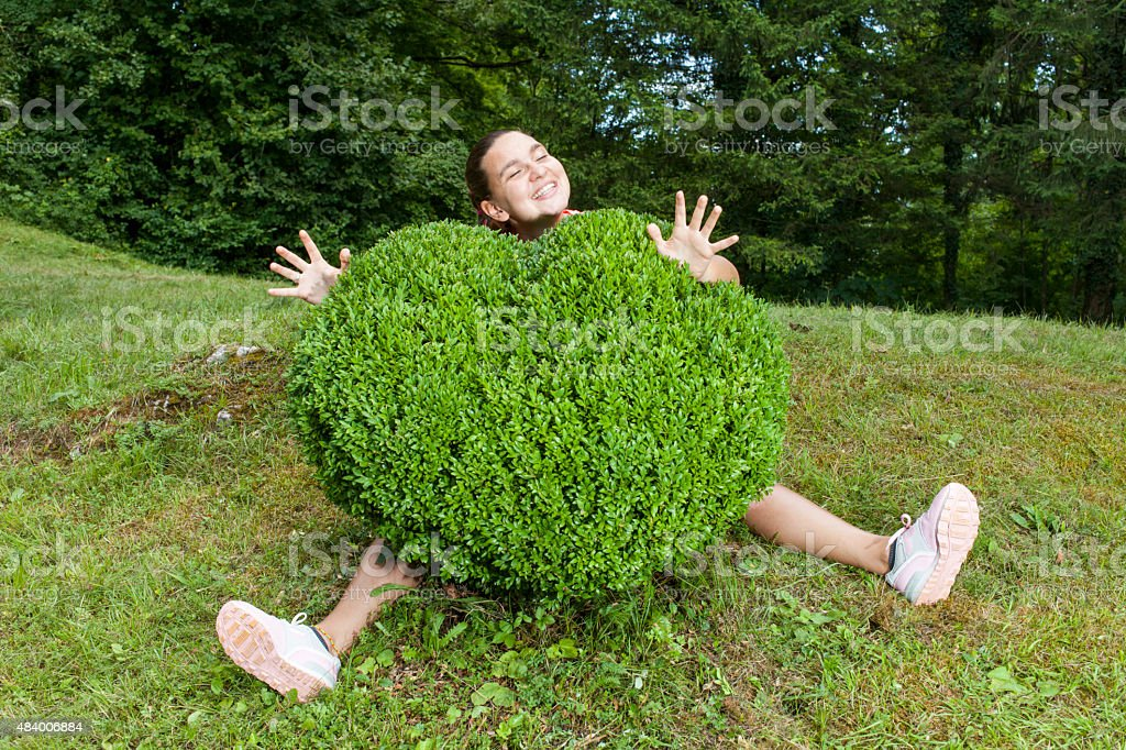 Pretty young woman hugging the boxwood stock photo