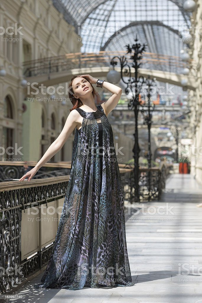 Pretty young woman in a fashionable flutter transparent cape royalty-free stock photo