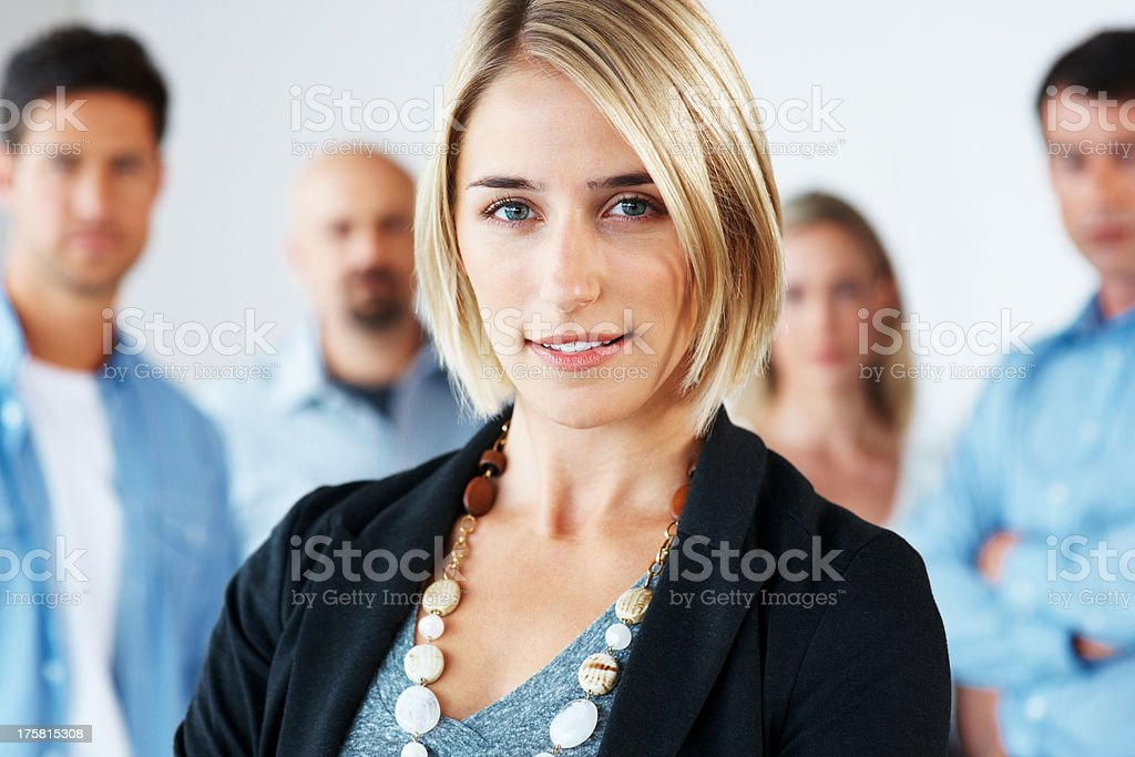 Pretty young woman in front with business team at the back stock photo