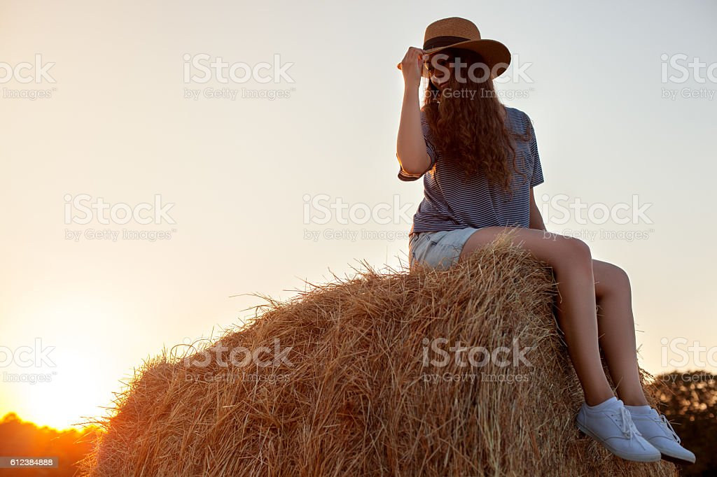 Pretty young woman in hat sitting on a hay bale stock photo