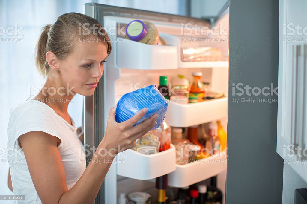 Pretty, young woman in her kitchen by the fridge stock photo