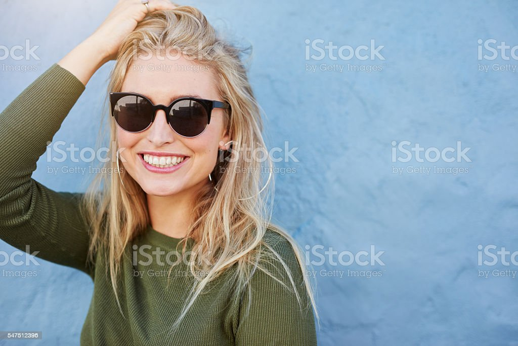 Pretty young woman in sunglasses smiling stock photo