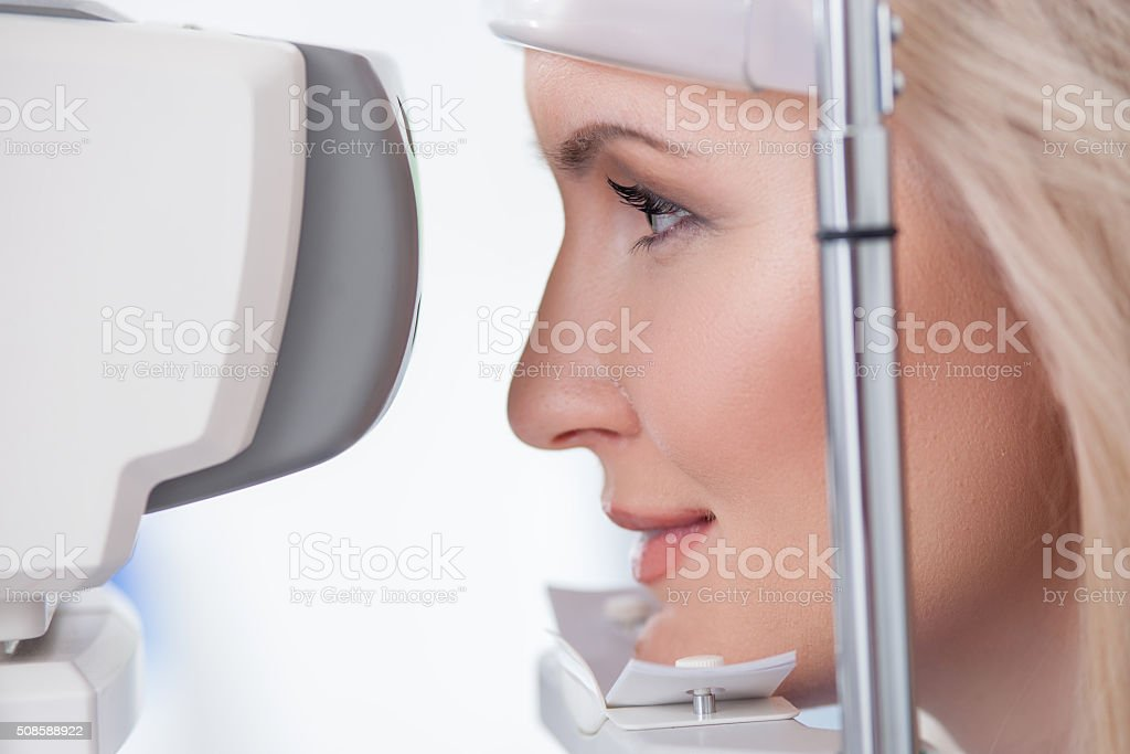 Pretty young woman is visiting eye doctor stock photo