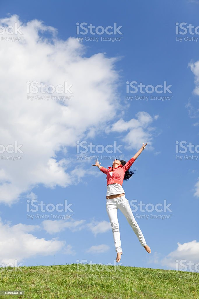 pretty young woman jumping on green grass royalty-free stock photo