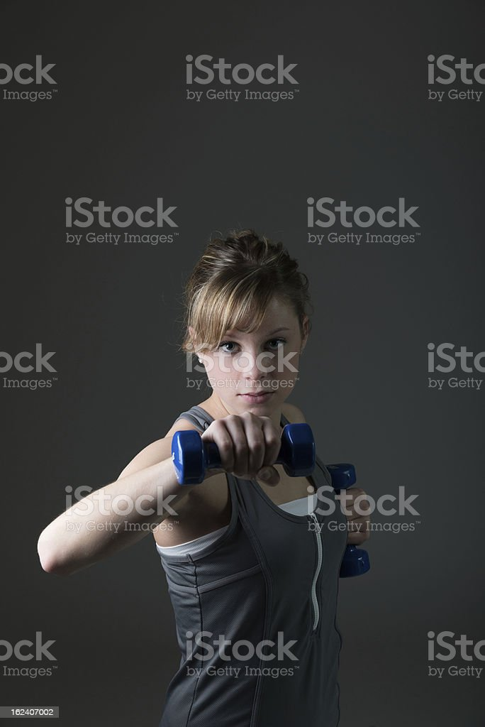 Pretty, young woman lifting dumbbells stock photo