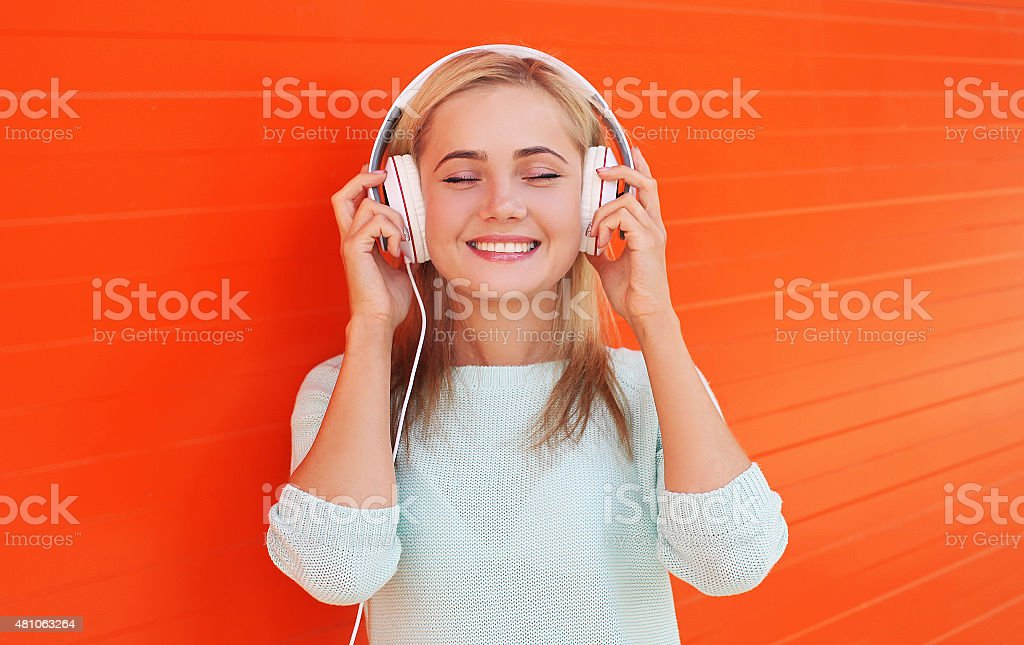 Pretty young woman listens and enjoys the music in headphones stock photo