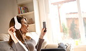 Pretty young woman listens and enjoys the music in headphones