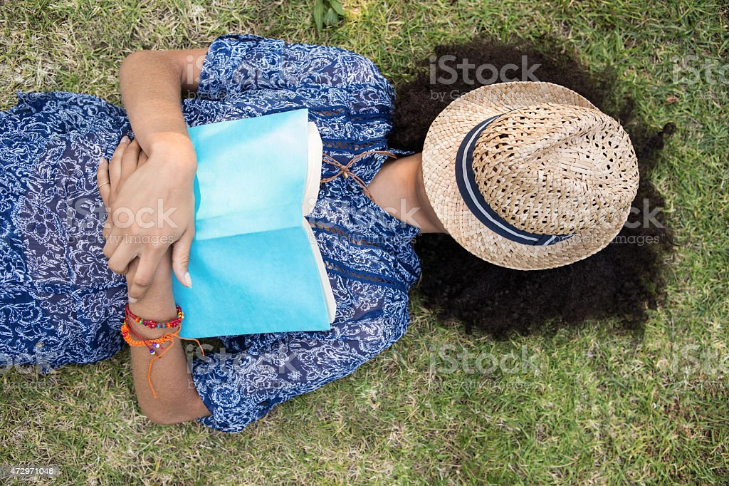Pretty young woman napping in park stock photo
