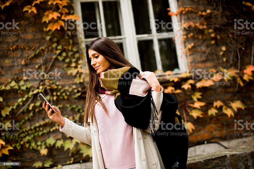 Pretty young woman on the city street with mobile phone stock photo