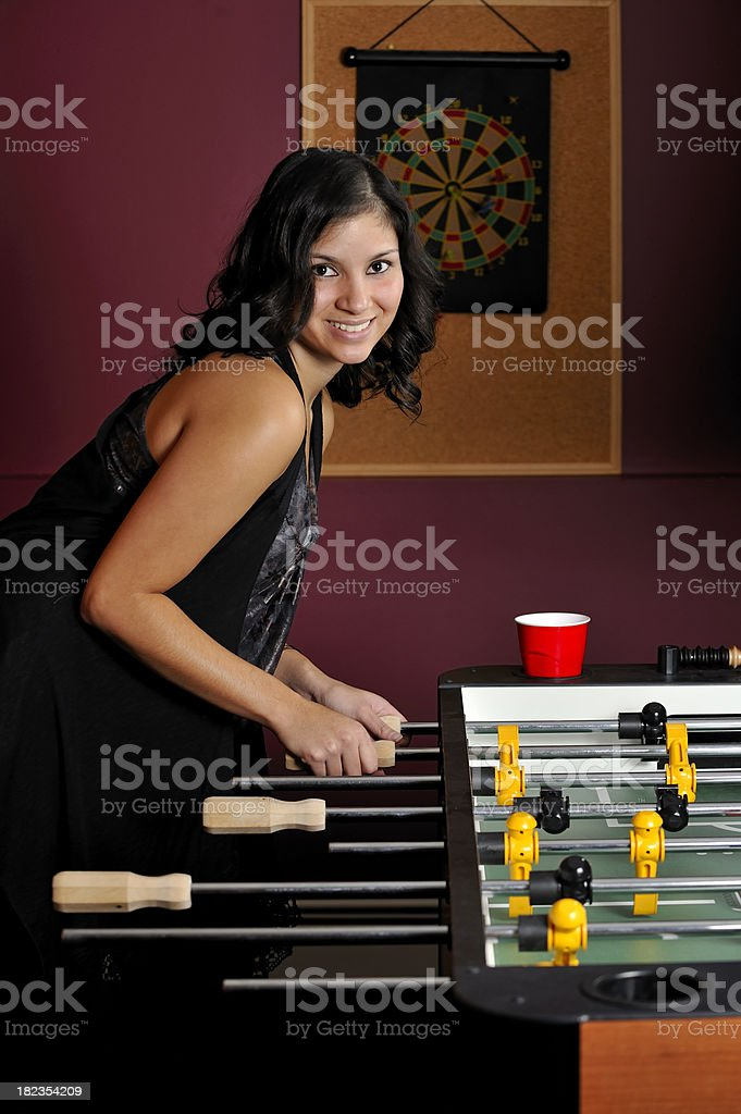 Pretty young woman playing foosball royalty-free stock photo