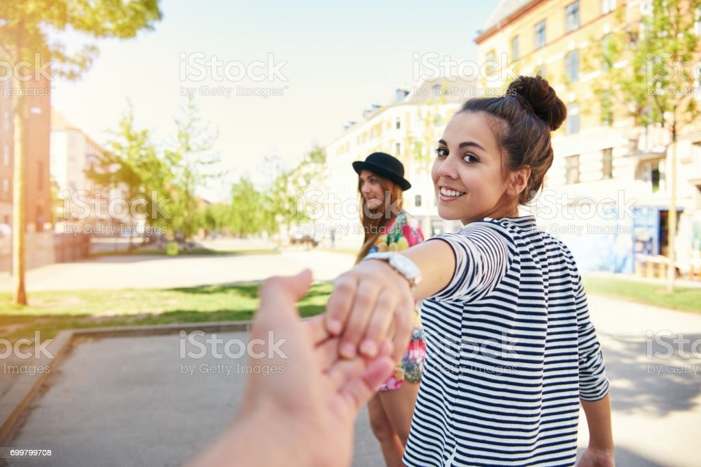 Pretty young woman pulling a man along stock photo