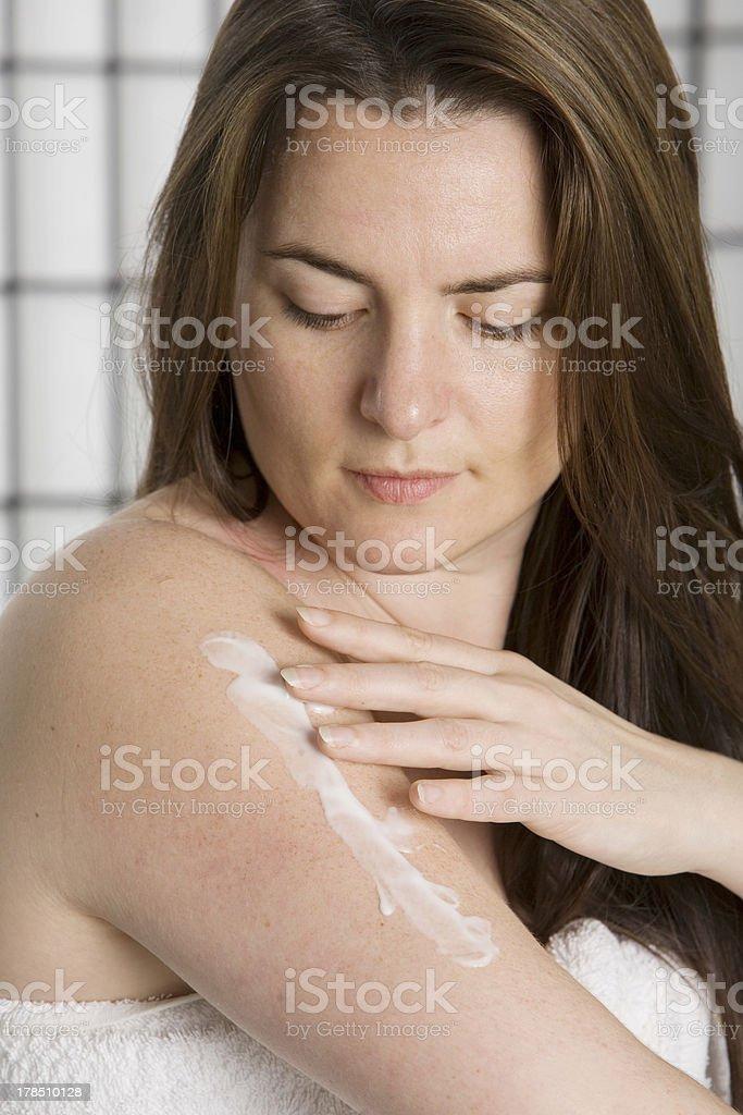 Pretty young woman puting on moisturizing lotion royalty-free stock photo