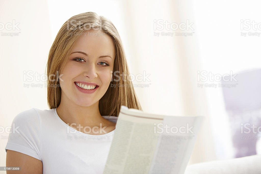 Pretty young woman reading a magazine royalty-free stock photo