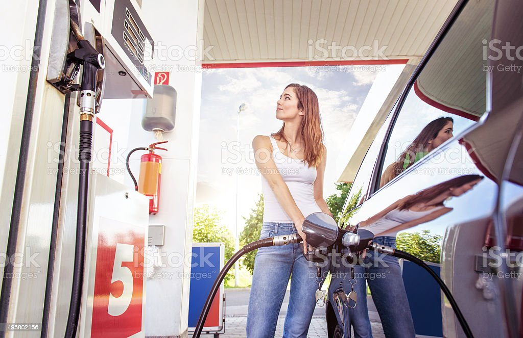 Pretty young woman refuel the car stock photo