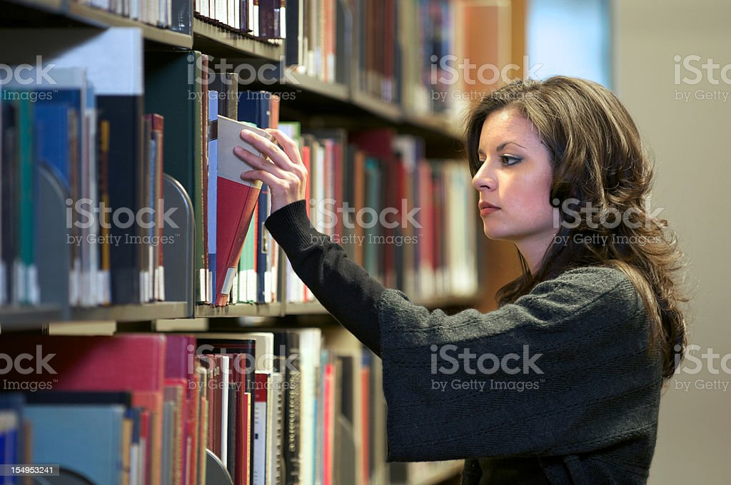 Pretty Young Woman Selecting Book in the Library royalty-free stock photo