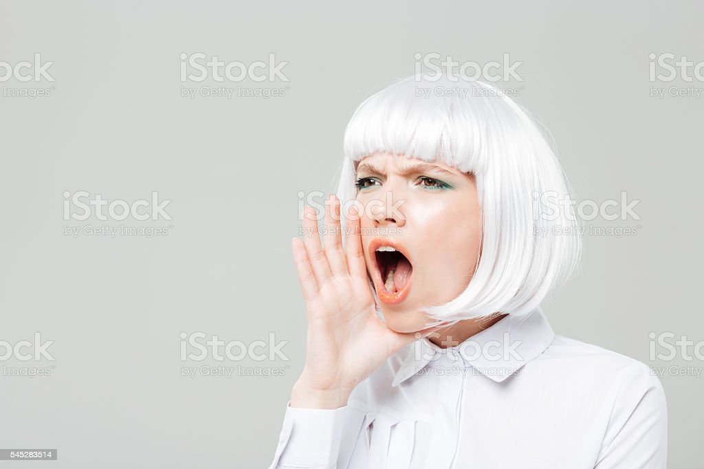 Pretty young woman shouting and calling for somebody stock photo