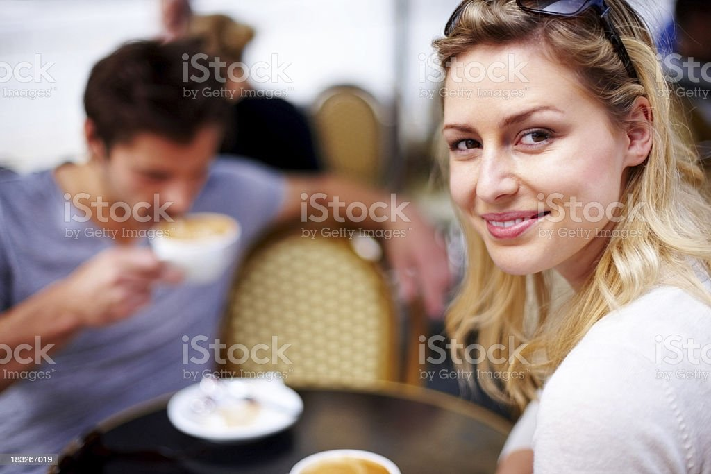 Pretty, young woman sitting at a cafeteria royalty-free stock photo
