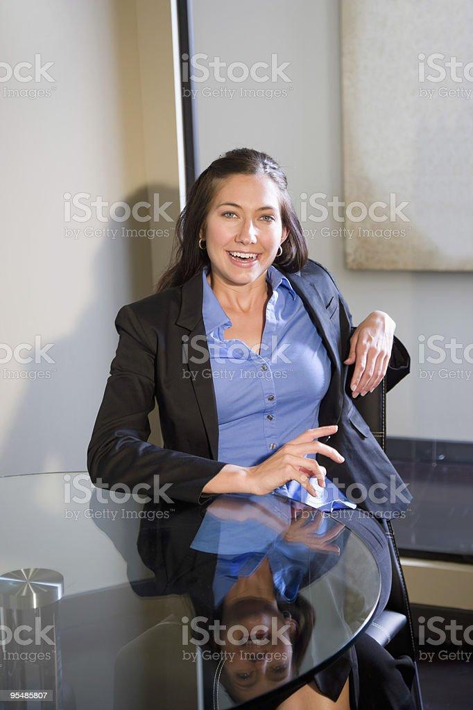 Hermosa Joven mujer sentada en la mesa redonda de vidrio foto de stock libre de derechos