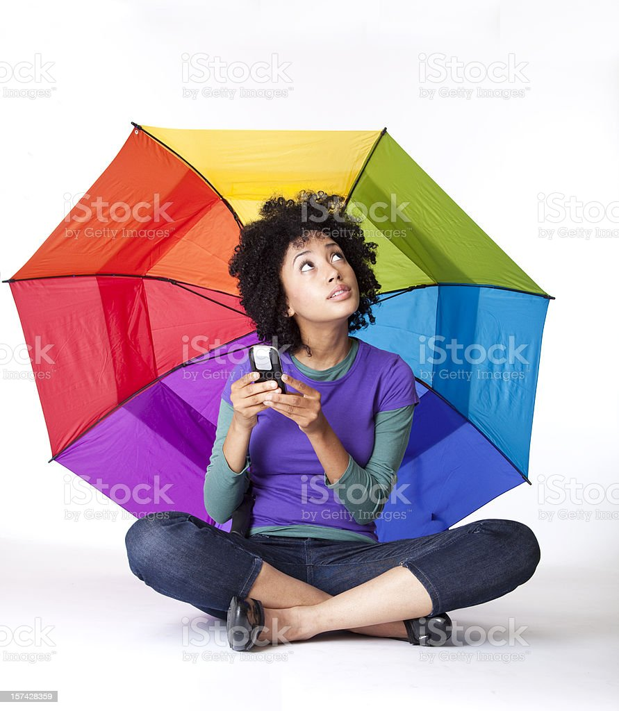 pretty young woman sitting cross-legged under umbrella, texting royalty-free stock photo