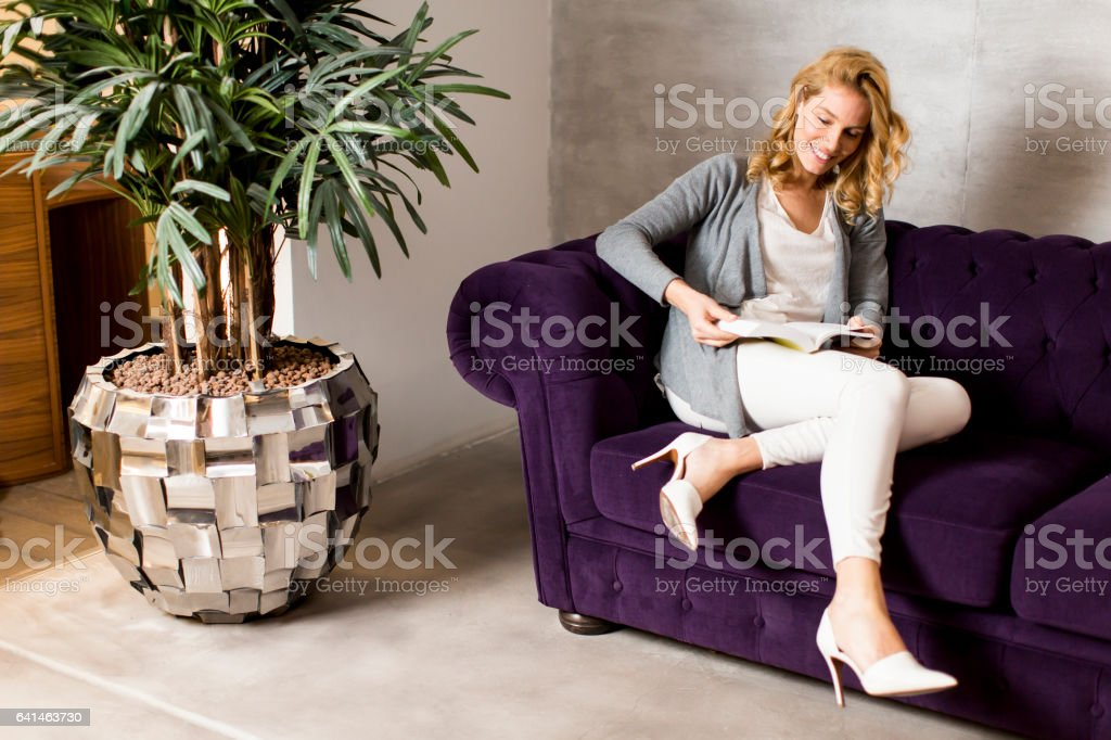 Pretty young woman sitting on the sofa in the room stock photo