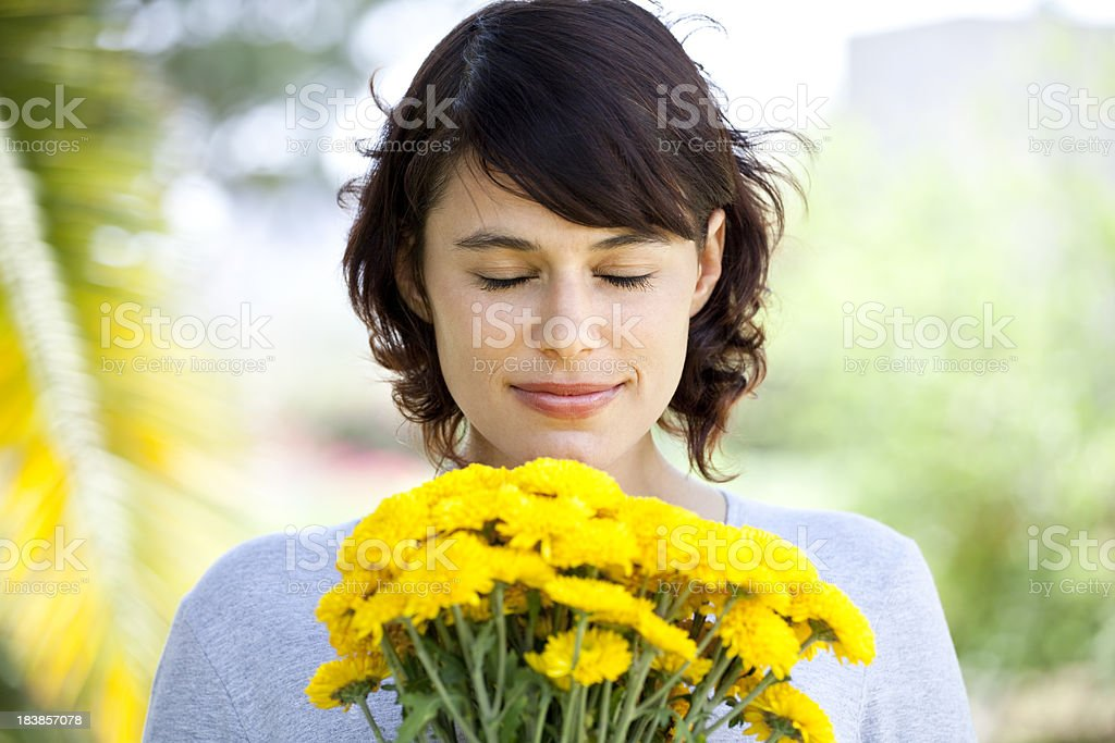 Pretty young woman smelling flowers royalty-free stock photo