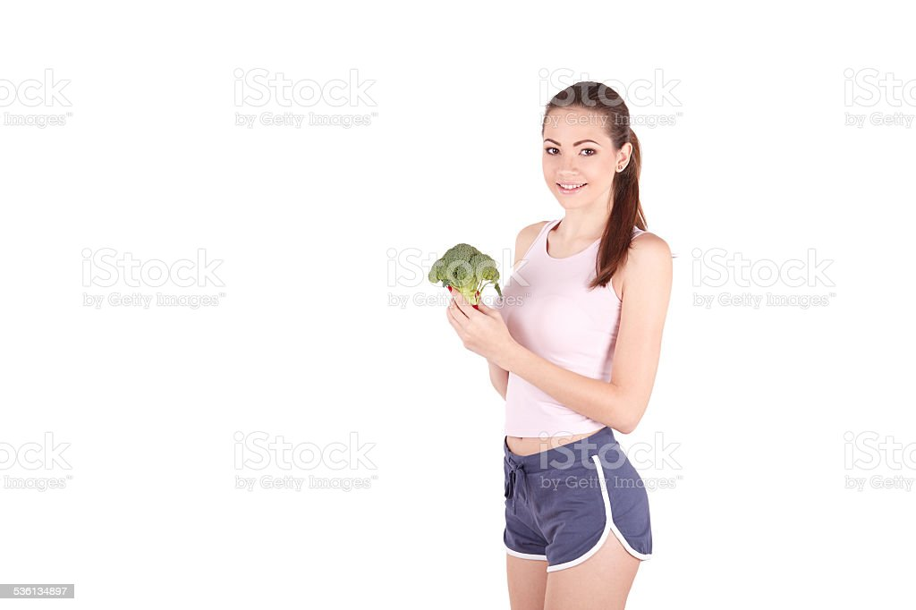 Pretty young woman smiling while holding some broccoli! royalty-free stock photo