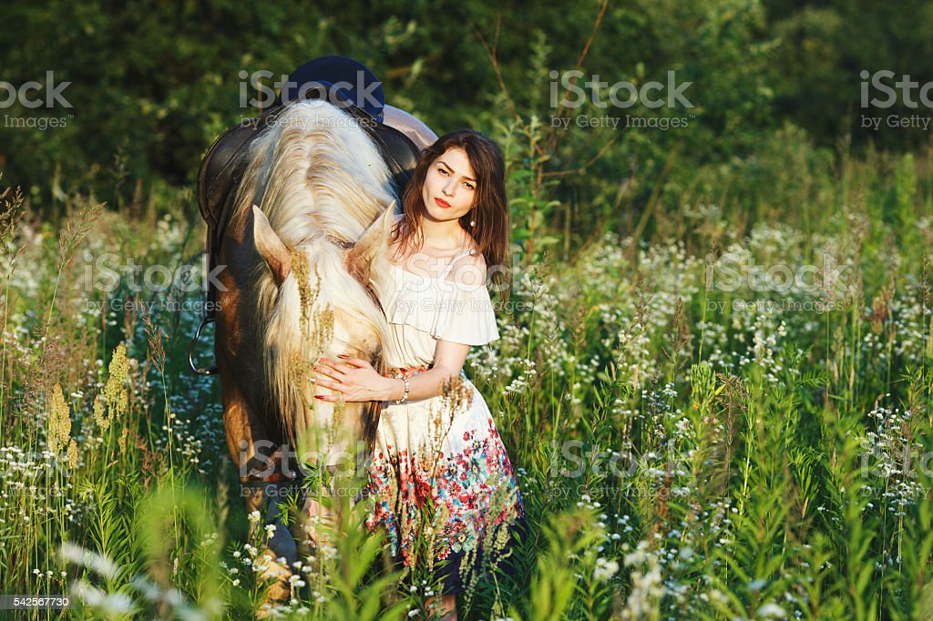 Pretty young woman standing with horse stock photo