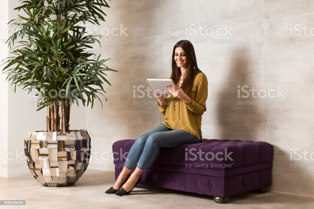 Pretty young woman using digital tablet in the room stock photo