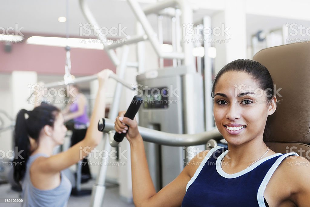 Pretty young woman using gym equipment smiles stock photo