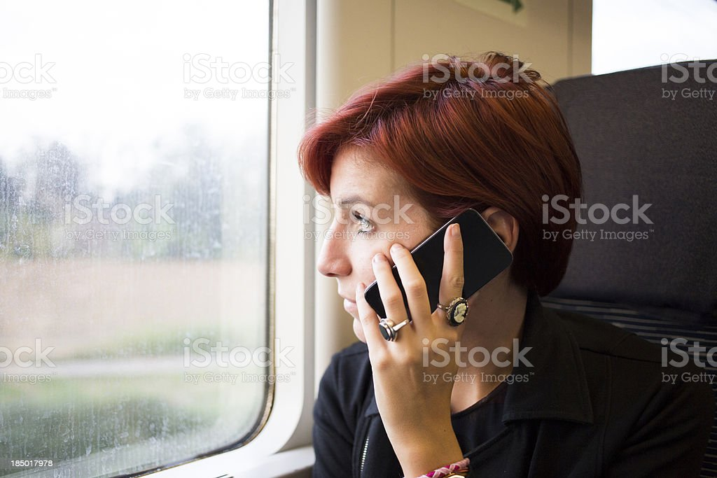 Pretty young woman using smartphone in train royalty-free stock photo