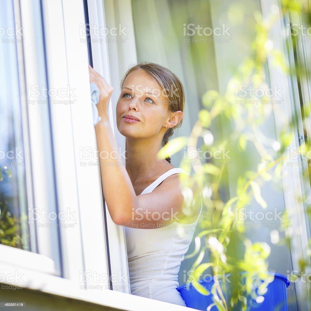 Pretty, young woman washing windows stock photo