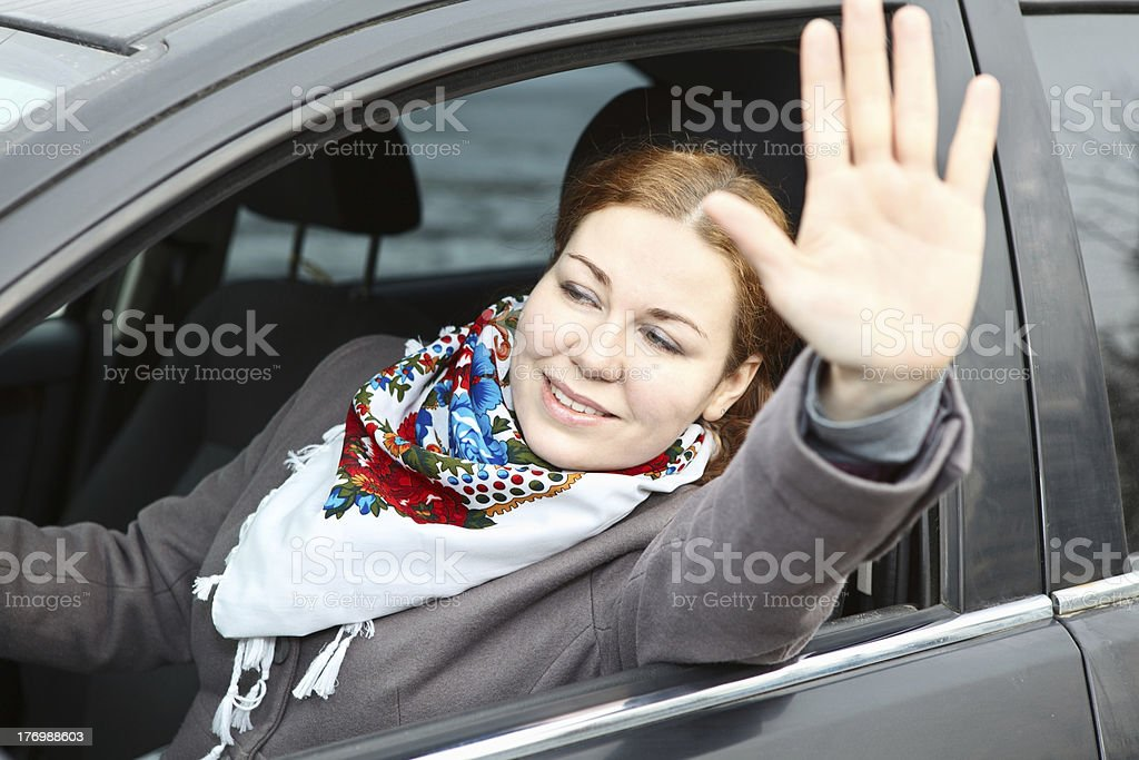Pretty young woman waving hers hand sitting in car stock photo