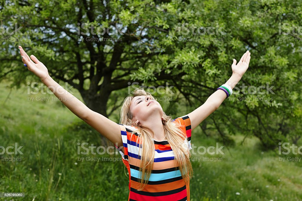 Pretty young woman with arms outstretched standing in nature stock photo