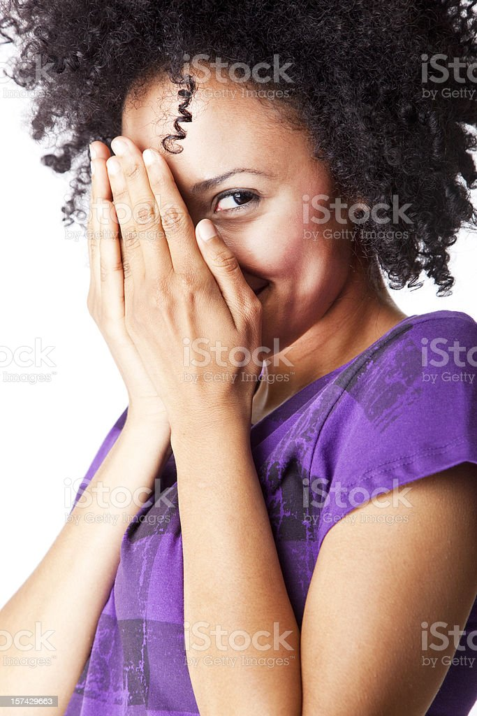 pretty young woman with curly hair, hiding face behind fingers royalty-free stock photo