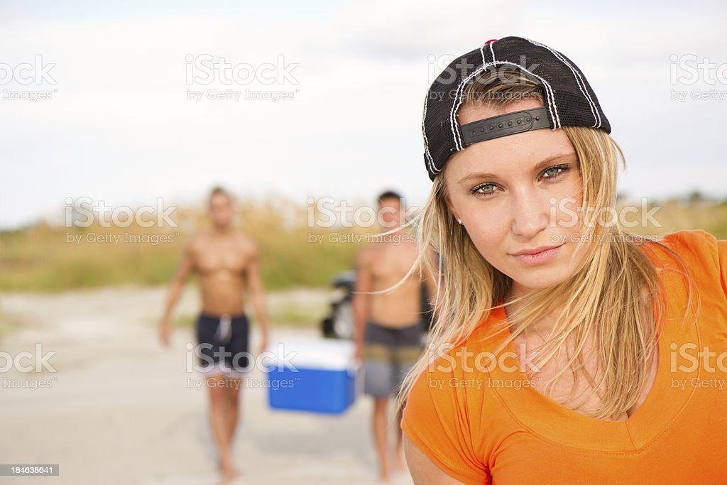 Pretty young woman with friends carry a cooler royalty-free stock photo