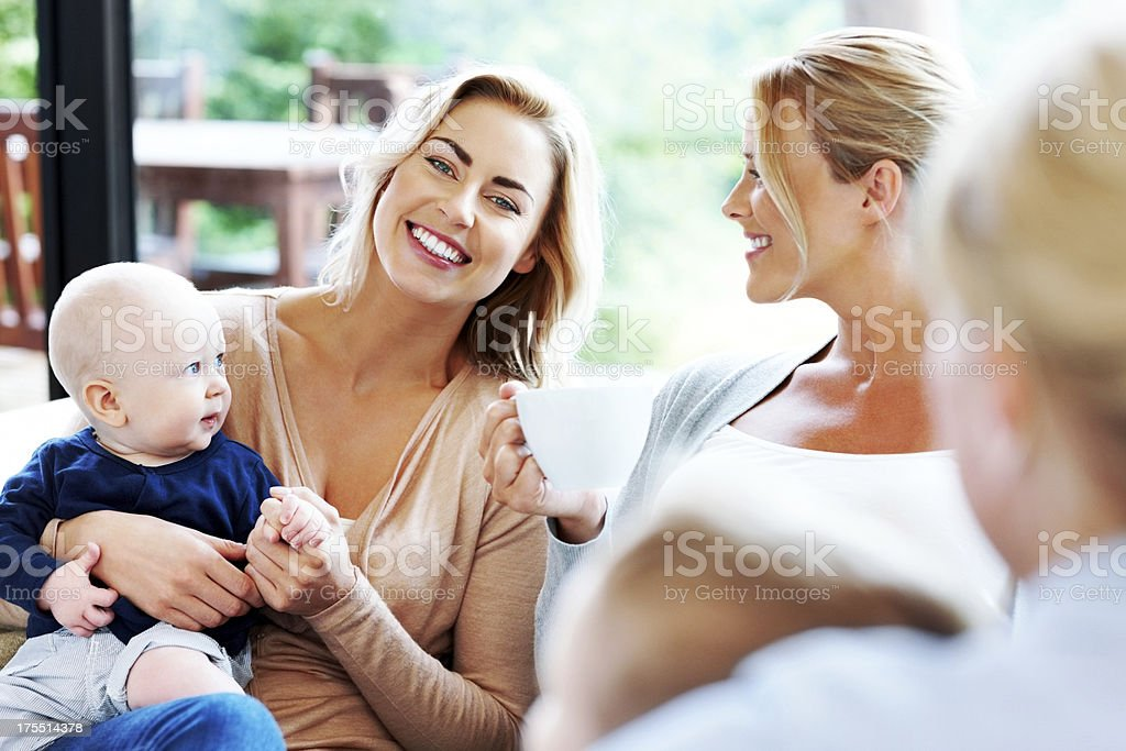 Pretty young woman with her kid and friends enjoying together royalty-free stock photo