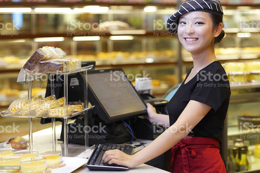 pretty young woman working in the bakery stock photo