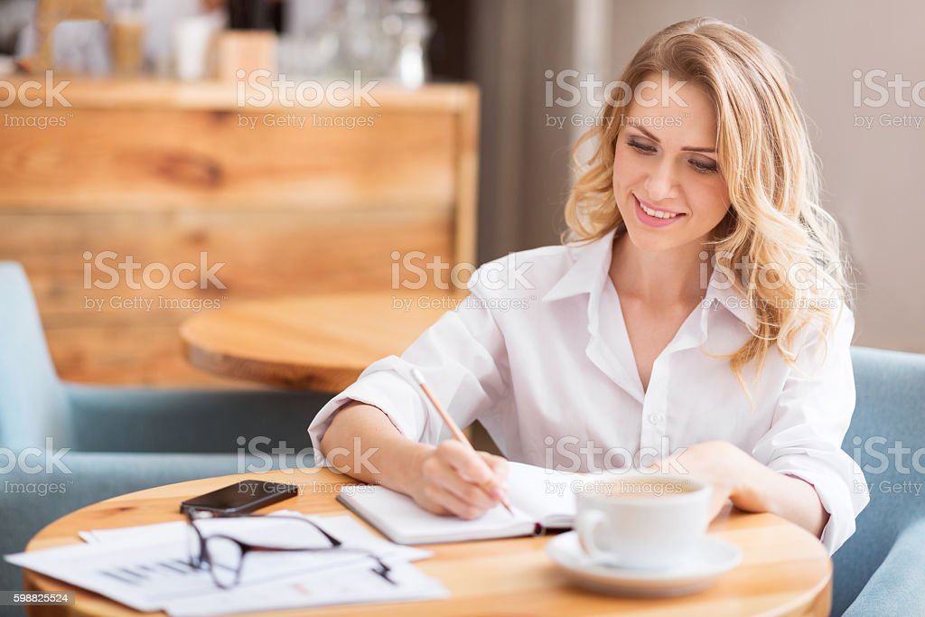 Pretty young woman writing something down stock photo