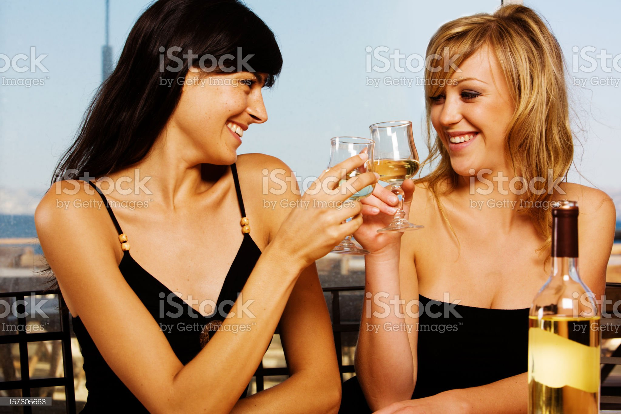 Pretty young women drinking white wine in restaurant royalty-free stock photo