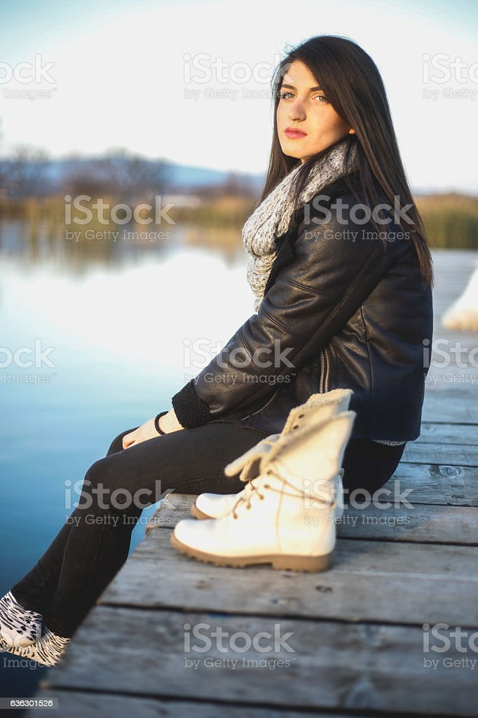 Pretty young women sitting on the pier and thinking stock photo