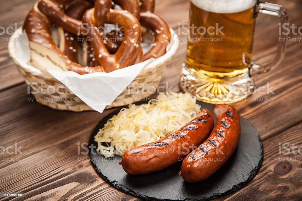 Pretzels, bratwurst and sauerkraut on wooden table stock photo