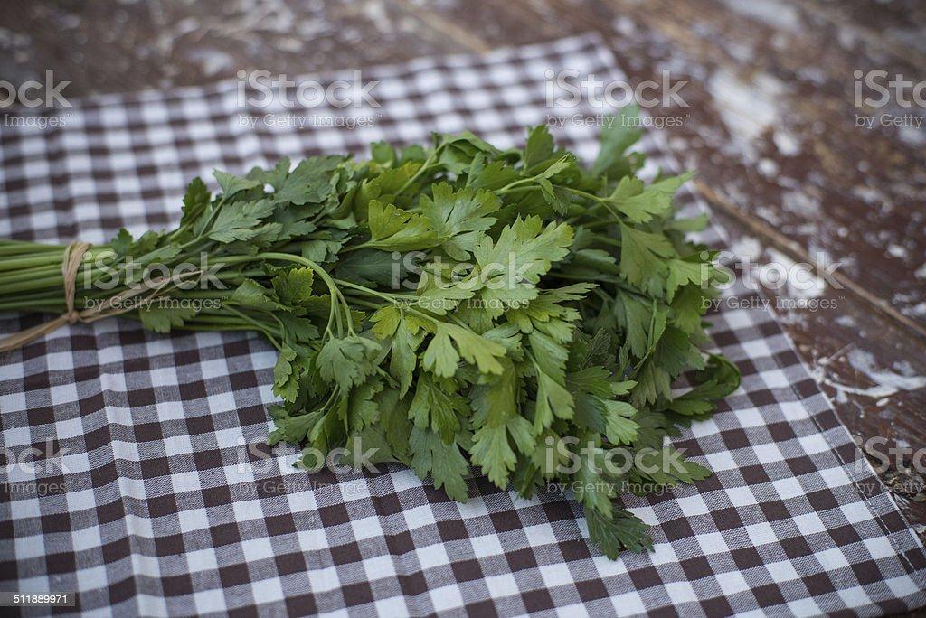 prezzemolo fresco mediterraneo su tavolo di legno stock photo