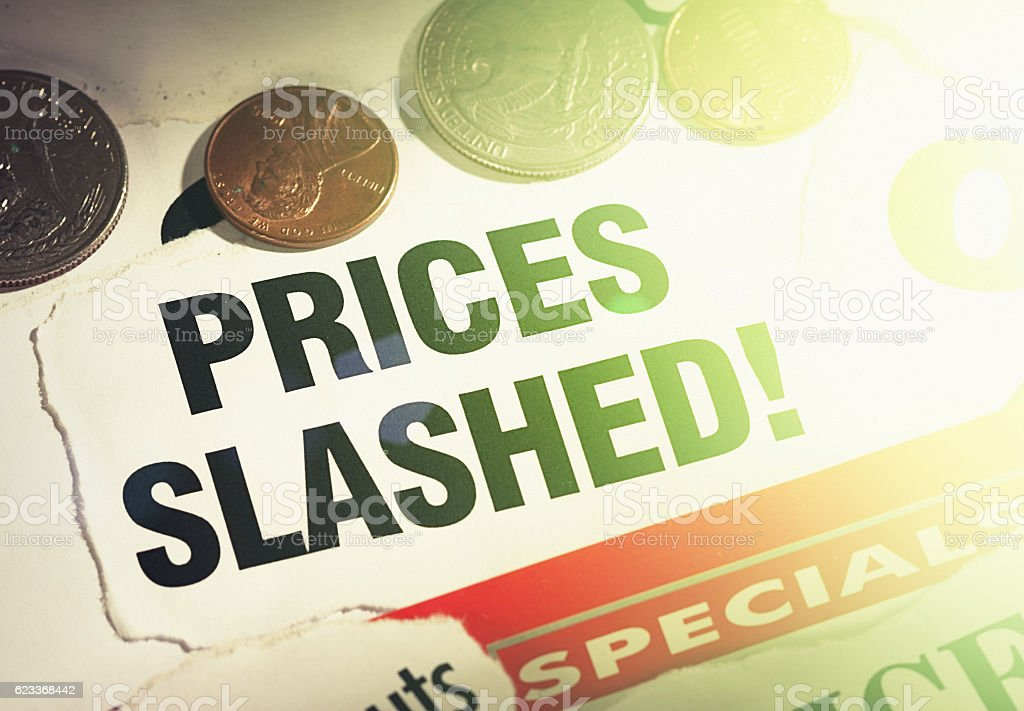 Prices slashed say newspaper cuttings held down by coins stock photo
